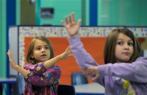 In this photo taken Oct. 9, 2013, Grace Whittaker, left, and Andria Kirkendall, right, learn sign language during a lesson at a home schooling co-operative at Andrews Air Force Base Md.