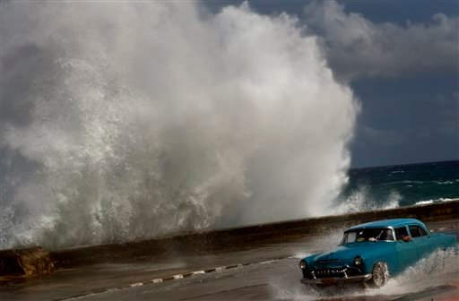 In this Thursday, Oct. 25, 2012 photo, a classic American car drives along a wet road as a wave crashes against the Malecon in Havana, Cuba.
