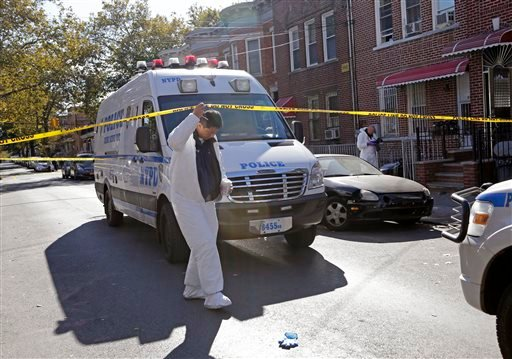 Crime scene specialists work at the scene of a fatal stabbing, Sunday, Oct. 27, 2013, in the Brooklyn borough of New York.