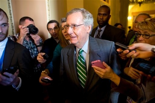 In this Oct. 14, 2013, file photo reporters surround Senate Minority Leader, Republican Mitch McConnell of Kentucky as he walks to the Senate floor after meeting with Senate Majority Leader, Democrat Harry Reid of Nevada in his office on Capitol Hill.