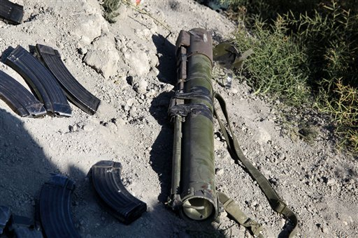 In this photo released by the Syrian official news agency SANA, destroyed weapons and ammunitions carried by Syrian rebels like at the site after they were killed by Syrian government forces according to SANA, near the Otaiba area, near Damascus, Syria.