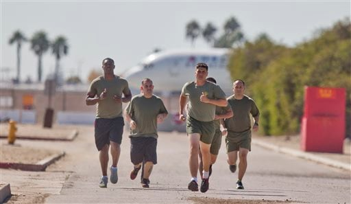 "In a Thursday, Oct. 17, 2013 photo, a group of sailors and Marines who failed the so-called ""tape test'' are led by an instructor on a three mile run. (AP Photo/Lenny Ignelzi)"