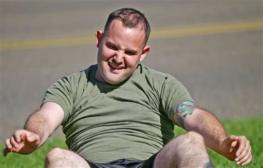 "In a Wednesday, Oct. 16, 2013 photo, overweight service member who failed the so-called ""tape test"" struggles doing sit ups during a workout. (AP Photo/Lenny Ignelzi)"