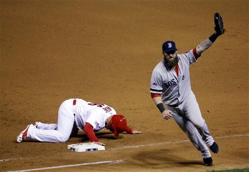 Boston Red Sox first baseman Mike Napoli celebrates after tagging out St. Louis Cardinals' Kolten Wong on a pick-off attempt to end Game 4 of baseball's World Series Sunday, Oct. 27, 2013, in St. Louis.