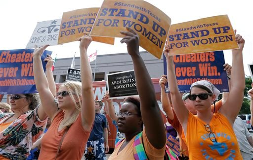 File - In this July 9, 2013 file photo, opponents and supporters of an abortion bill hold signs near a news conference outside the Texas Capitol, in Austin, Texas. (AP)