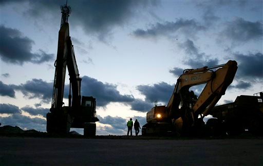 In early morning darkness, workers prepare heavy machinery for the day as rebuilding work continues on the beach area of Seaside Heights and Seaside Park, N.J., Tuesday, Oct. 29, 2013.