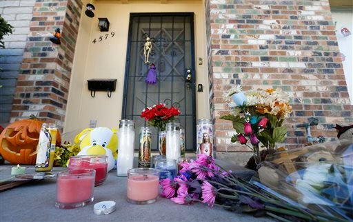 A makeshift memorial has been set up in front of the Moore home on Monday Oct. 28, 2013, in Phoenix, to remember the four shooting victims.