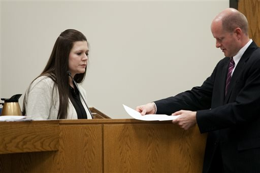 Alexis Somers is handed documents by Chad Grunander, Utah County prosecutor, while testifying at the trial of her father Martin MacNeill at the Fourth District Court in Provo Wednesday, Oct. 30, 2013. (AP)