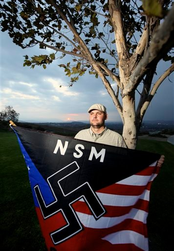 In this Oct. 22, 2010 file photo, Jeff Hall holds a neo Nazi flag while standing at Sycamore Highlands Park near his home in Riverside, Calif. Hall's 10-year-old son is being charged with murdering his father.