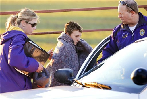 Logan Parker, 12, is put in a school security car after a bus accident sent the kids and bus into a creek Thursday, Oct. 31, 2013, in Butler County, Kan. (AP)