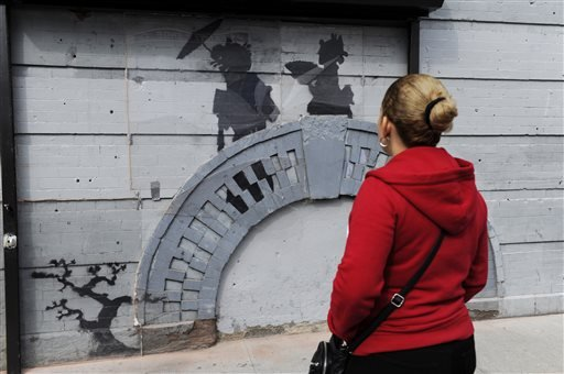 In this Oct. 19, 2013, file photo, a woman looks at work by British graffiti artist Banksy in New York's Brooklyn Borough.