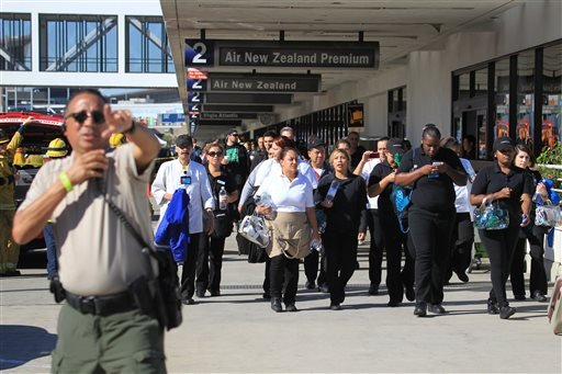 Passengers are directed outside Terminal 2 at Los Angeles International Airport on Friday Nov. 1, 2013, after shots were fired, prompting authorities to evacuate a terminal and stop flights .