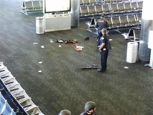 In this photo provided to the AP, which has been authenticated based on its contents and other AP reporting, police officers stand near an unidentified weapon in Terminal 3 of the Los Angeles International Airport on Friday, Nov. 1, 2013. (AP)
