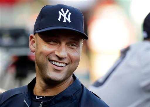 New York Yankees shortstop Derek Jeter laughs while standing in the dugout with teammates during a baseball game against the Texas Rangers in Arlington, Texas.  (AP Photo/LM Otero, File)