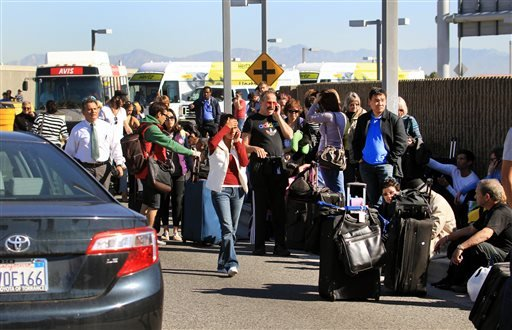 Passengers evacuate the Los Angeles International Airport on Friday Nov. 1, 2013, in Los Angeles. (AP)