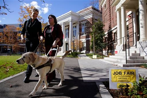 """Marie Hennessy, president of the Perkins School for the Blind alumni association leaves a job fair for the visually impaired with her guide dog """"Azalea"""" and a volunteer guide, left, on the Radcliffe Yard campus in Cambridge, Mass., Thursday, Oct. 24, 2013"""
