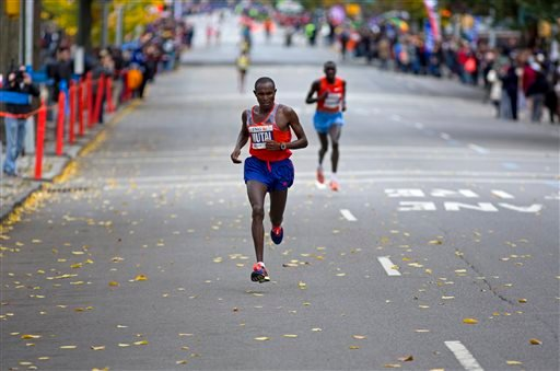 Geoffrey Mutai of Kenya runs along Fifth Avenue during the New York City Marathon Sunday, Nov. 3, 2013. In a double victory for Kenya, Mutai successfully defended his title and Priscah Jeptoo rallied to win the women's race. (AP Photo/Craig Ruttle)