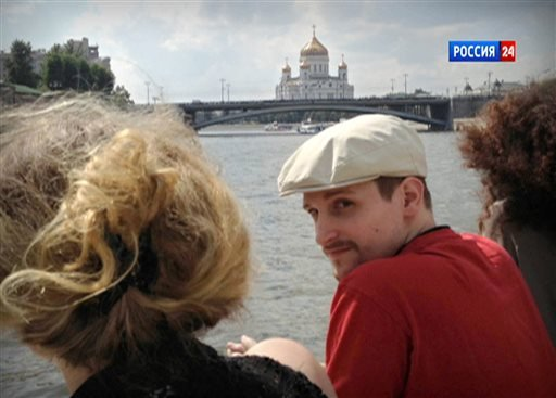 Former National Security Agency systems analyst Edward Snowden looks over his shoulder during a boat trip on the Moscow River in Moscow, with the Christ the Savior Cathedral in the background.