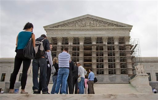 This Oct. 7, 2013 file photo shows people wait in line to enter the Supreme Court in Washington.