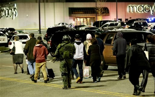An official, center, wearing tactical gear leads a group of people out of the Garden State Plaza Mall during a lockdown following reports of a shooter, Tuesday, Nov. 5, 2013, in Paramus, N.J. (AP Photo/Julio Cortez)
