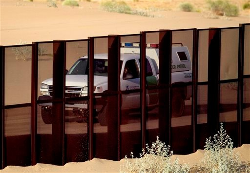 In this July 28, 2010, file photo, a U.S. border patrol vehicle drives along the U.S.-Mexico border fence near Yuma, Ariz., as seen from the outskirts of San Luis Rio Colorado, Mexico.