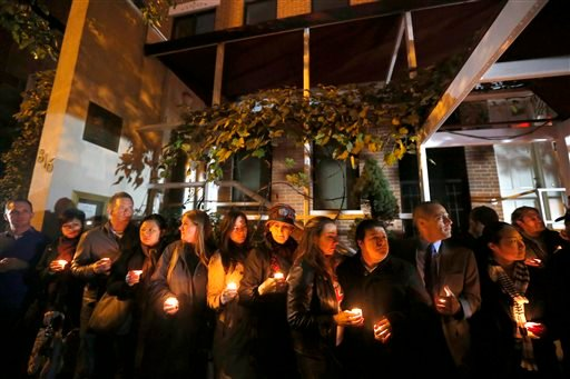 Friends and former employees of Chicago chef Charlie Trotter gather outside Trotter's former restaurant for a candlelight memorial Tuesday, Nov. 5, 2013, in Chicago.