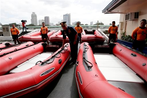 Philippine Coast Guard Chief Rear Adm. Rodolfo Isorena checks newly-acquired rubber boats following blessing ceremony Wednesday, Nov. 6, 2013 in Manila, Philippines. (AP Photo/Bullit Marquez)