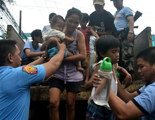 In this Thursday, Nov. 7, 2013 photo, residents living near the slopes of Mayon volcano are evacuated to public schools by police in anticipation of the powerful typhoon Haiyan that threatened Albay province and several provinces in central Philippines.