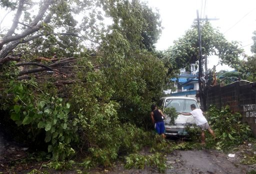 Residents clear the road after a tree was toppled by strong winds and damaged a van at the onslaught of powerful typhoon Haiyan that hit the island province of Cebu, Philippines Friday Nov. 8, 2013.