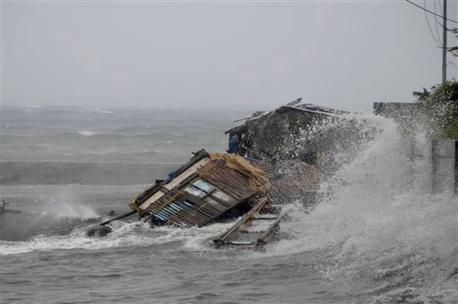 A house is engulfed by the storm surge brought about by powerful typhoon Haiyan that hit Legazpi city, Albay province Friday Nov.8, 2013 about 520 kilometers ( 325 miles) south of Manila, Philippines.