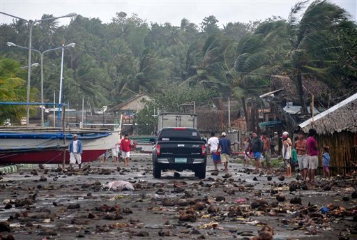 Debris litter the road by the coastal village in Legazpi city following a storm surge brought about by powerful Typhoon Haiyan in Albay province Friday, Nov. 8, 2013, about 520 kilometers ( 325 miles) south of Manila, Philippines.