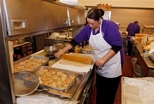 In this Jan. 18, 2012, file photo, Alexes Garcia makes cinnamon rolls for student's lunch in the kitchen at Kepner Middle School in Denver.