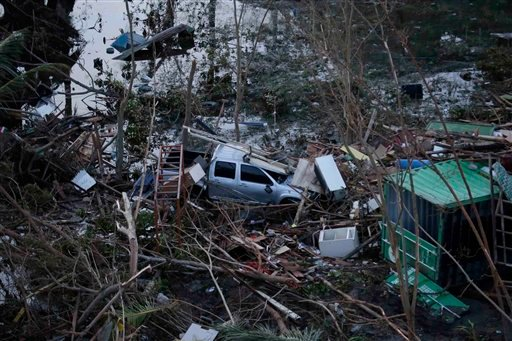 A vehicle lies amidst debris brought about by powerful typhoon Haiyan that hit Tacloban city, in Leyte province in central Philippines Saturday, Nov. 9, 2013.