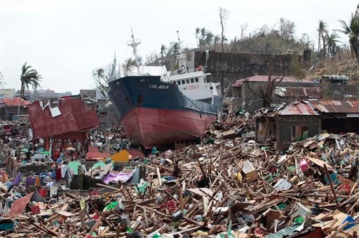 A ship lies on top of damaged homes after it was washed ashore in Tacloban city, Leyte province, central Philippines on Sunday, Nov. 10, 2013.