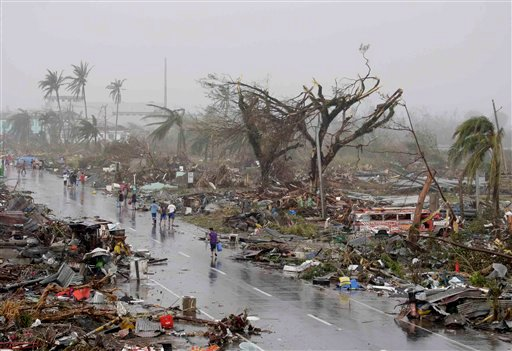 Resident walk past damaged houses in Tacloban city, Leyte province, central Philippines on Sunday, Nov. 10, 2013.