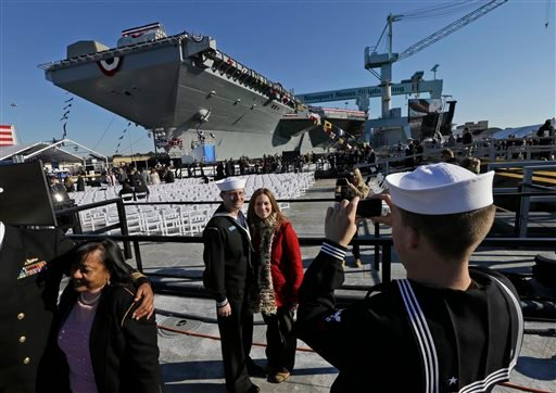 U.S. Navy Bosons mate, Ben Hansen and his wife Jessica, of Edmore Mich., are photographed in front of the Navy's newest nuclear powered aircraft carrier USS Gerald R. Ford for the christening of the ship at the Newport News Shipbuilding in Newport News.