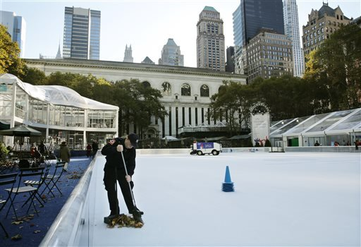 Debris is swept from the ice skating rink at Bryant Park in New York, Sunday, Nov. 10, 2013. A shooting at the ice rink at the popular midtown Manhattan park late Saturday sent two men to the hospital with non-life-threatening injuries, police said.