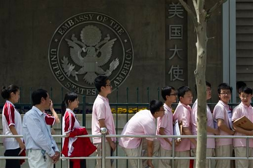 In this May 2012 file photo, Chinese students wait outside the U.S. Embassy for their visa application interviews in Beijing, China, Wednesday, May 2, 2012.