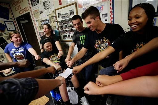 Iraq war veteran Jerral Hancock, sitting on an electric wheelchair, and members of Operation All The Way Home(OATH) chant their slogans after a meeting at Lancaster High School on Monday, Oct. 21, 2013, in Lancaster, Calif.