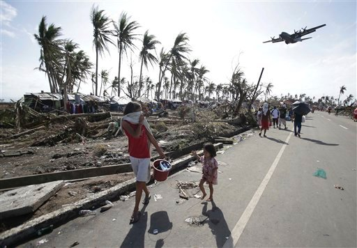 Survivors look at a military C-130 plane which arrives at typhoon-ravaged Tacloban city, Leyte province central Philippines on Monday, Nov. 11, 2013.