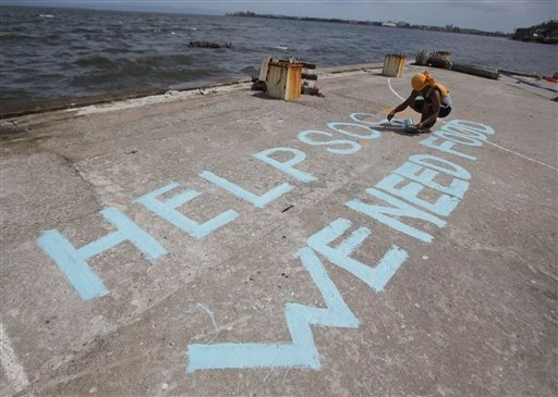 A survivor writes a message on their port to call for help at typhoon-ravaged Tacloban city, Leyte province central Philippines on Monday, Nov. 11, 2013.