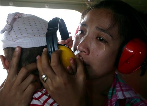 A mother cries in relief upon boarding a Philippine Air Force helicopter, Monday Nov. 11, 2013 following Friday's typhoon Haiyan which lashed Guiuan township, Eastern Samar province, central Philippines.