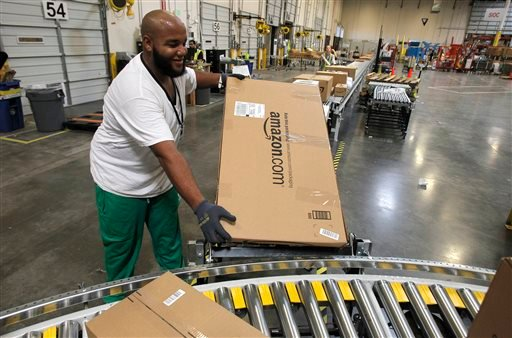 FILE - In this Nov. 11, 2010 file photo, Leacroft Green places a package on the belt at an Amazon.com fulfillment center, in Goodyear, Ariz. (AP)
