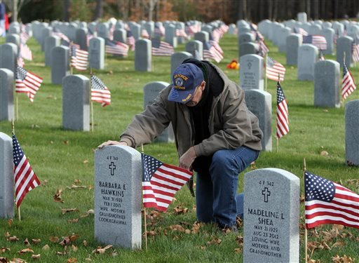 James Higgins of Webster, N.H. stops to pay respect on Veterans Day at the New Hampshire State Veterans Cemetery, Monday, Nov. 11, 2013 in Boscawen, N.H. (AP)