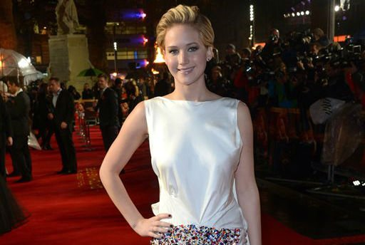 """American actress Jennifer Lawrence poses for photographers as she arrives on the red carpet for the World Premiere of """"The Hunger Games: Catching Fire,"""" on Monday Nov. 11, 2013, in Leicester Square, London."""