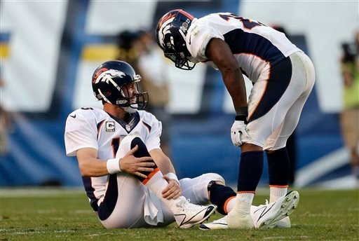 Denver Broncos quarterback Peyton Manning, left, holds his leg after being injured while playing the San Diego Chargers as teammate running back Knowshon Moreno, right, talks with him during the second half of a NFL football game on Sunday, Nov. 10, 2013,