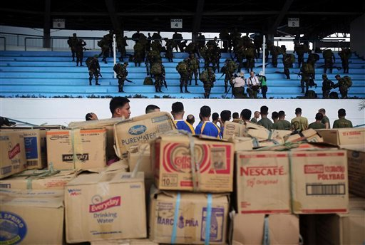Philippine soldiers stand near relief supplies for victims of Typhoon Haiyan at Villamor Airbase, Tuesday, Nov. 12, 2013 in Manila, Philippines.