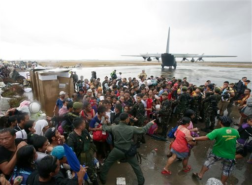 Typhoon survivors rush to get a chance to board a C-130 military transport plane in Tacloban city, Leyte province, central Philippines, Tuesday, Nov. 12, 2013.