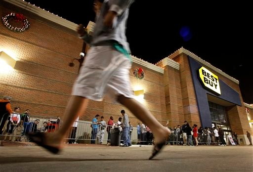 In this Thursday, Nov. 22, 2012, file photo, shoppers stand in line outside a Best Buy department store before the store's opening at midnight.