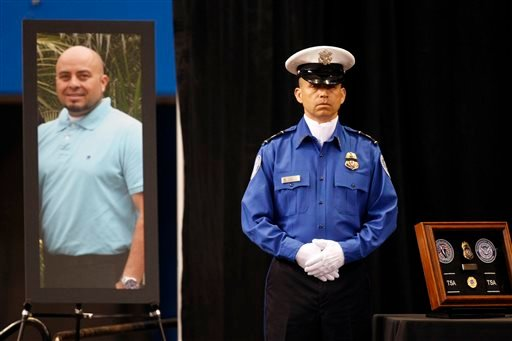 A Transportation Security Administration officer stand in front of a portrait of slain TSA officer Gerardo Hernandez during his public memorial at the Los Angeles Sports Arena, Tuesday, Nov. 12, 2013. (AP)